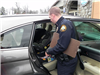 Officer Installs Child Safety Seat in Car