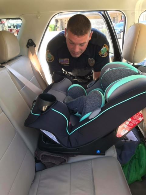 Officer Craig installing a child safety seat